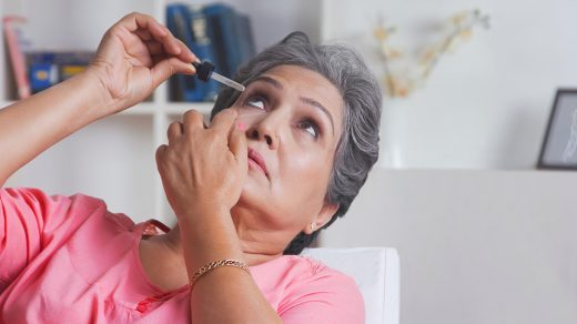 Old woman putting eye drops